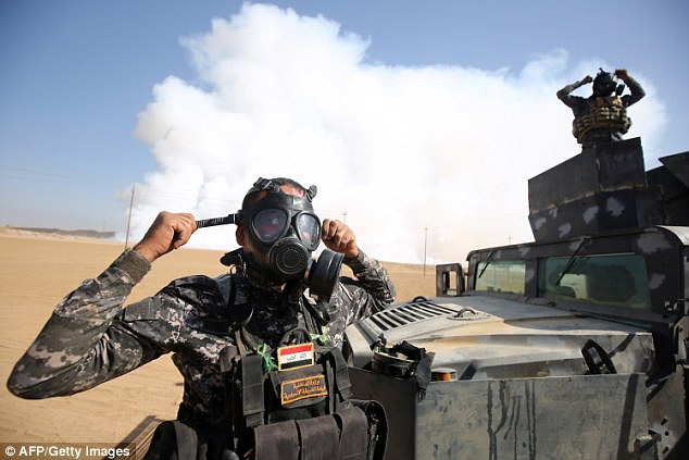 39a17e2e00000578-0-an_iraqi_soldier_puts_on_a_gas_mask_as_smoke_billows_in_the_back-a-36_1477590337455